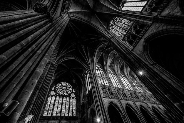 Low angle shot of a cathedral ceiling with windows in black and white