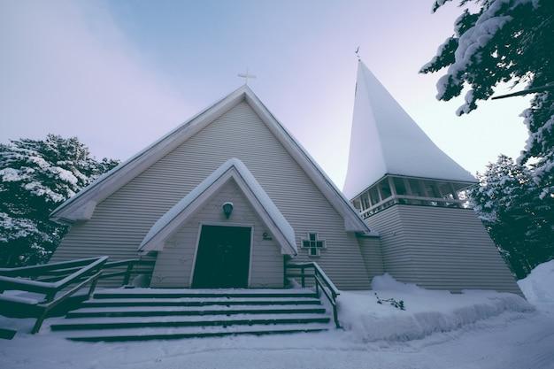 Inquadratura dal basso di una cappella ricoperta di neve spessa in inverno