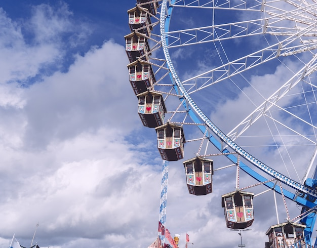 Low angle shot of a circular carousel revolving under a sky full of clouds