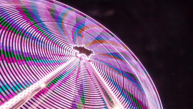 Low angle shot of a colorful amusement park ride taken at night with a pitch