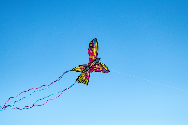 Low angle shot of a colorful kite with butterfly shape