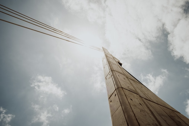 Low angle shot of a concrete column with cables against a bright cloudy sky