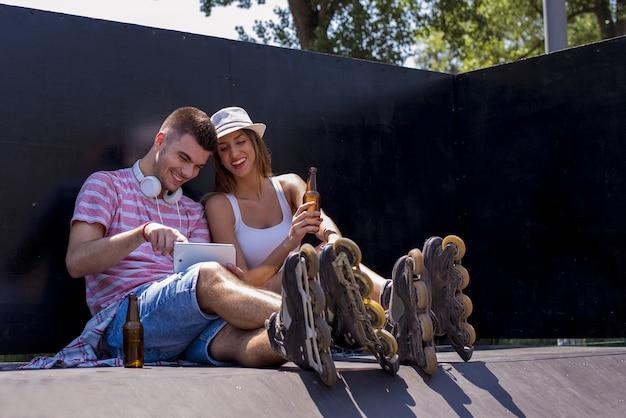 Inquadratura dal basso di una coppia con pattini a rotelle seduti in uno skatepark sotto la luce del sole