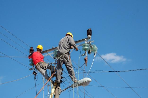 Inquadratura dal basso di guardalinee elettrici che lavorano sul palo