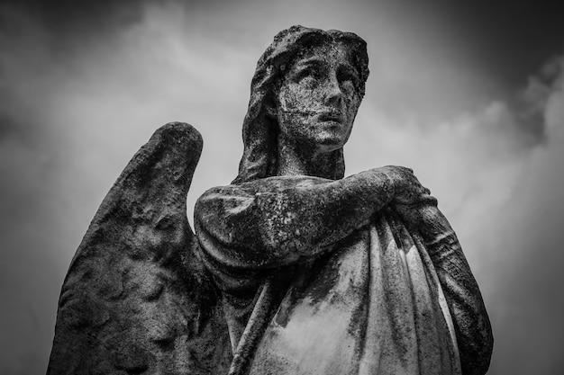 Low angle shot of a female statue with wings in black and white