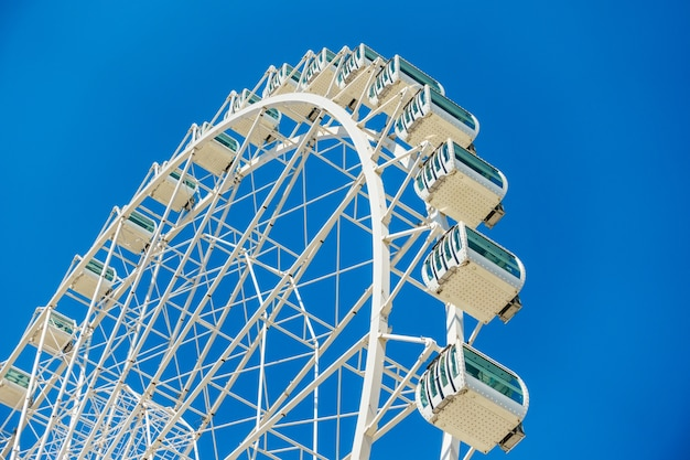 Low angle shot of a ferris wheel under a clear blue sky