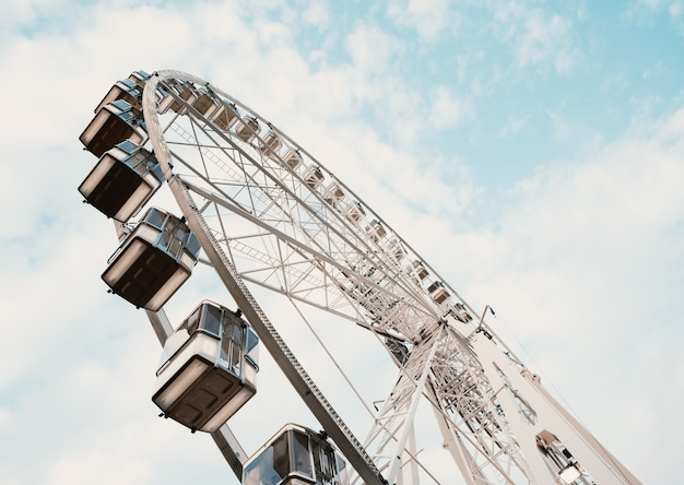 Low angle shot of a ferris wheel with cloudy blue sky