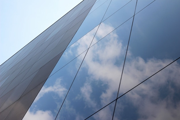 Low angle shot of a glass high-rise business building with a reflection of clouds and the sky on it