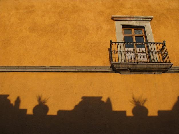 Inquadratura dal basso di una finestra di vetro con una recinzione metallica e ombre su una parete gialla di un edificio