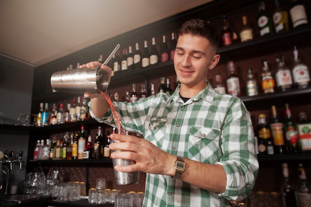 Low angle shot of a handsome cheerful bartender preparing a cocktail, copy space