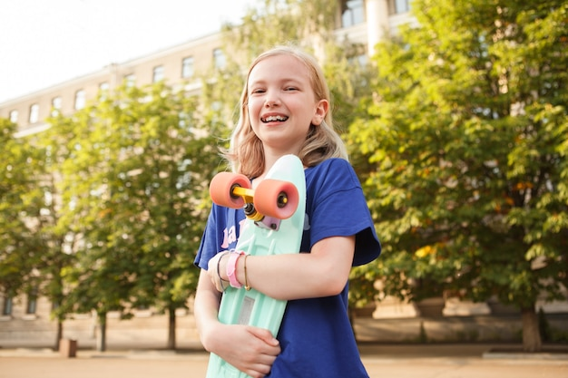 Low angle shot of a happy girl laughing, hugging her penny boark outdoors