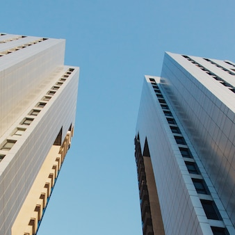 Low angle shot of high-rise buildings under a clear blue sky