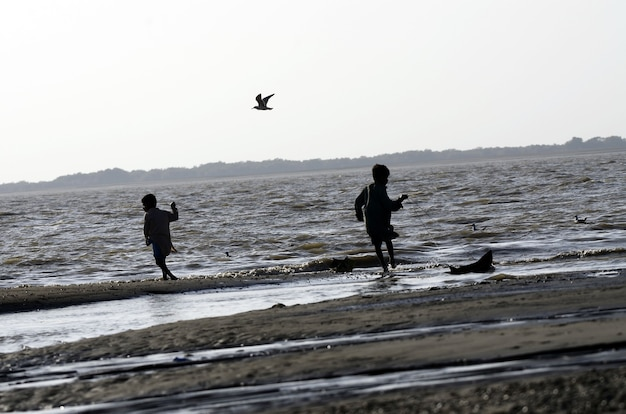Low angle shot of kids walking on the beach