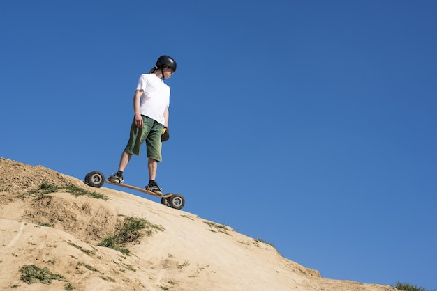 Low angle shot of a male mountainboarder on a hill slope