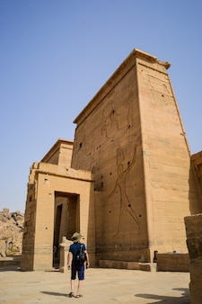 Low angle shot of a male standing in front of isis aswan temple in egypt