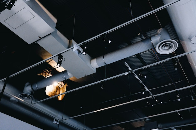 Low angle shot of a metal black ceiling with white ventilation pipes
