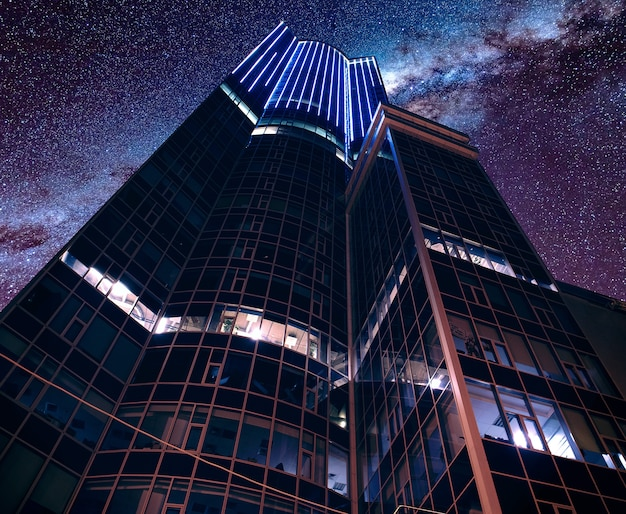 Low angle shot of a modern futuristic business architecture under a breathtaking starry sky