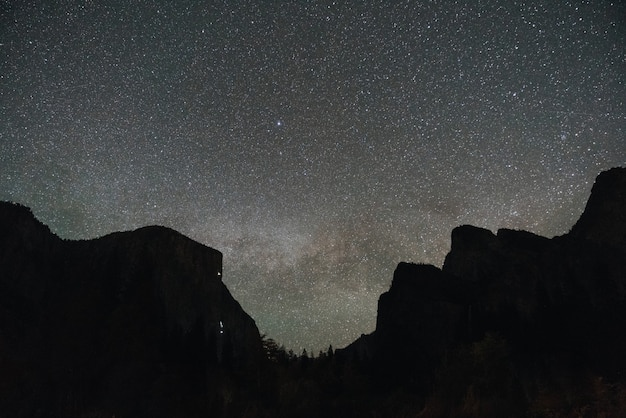 Low angle shot of a mountainous scenery under the magical night sky