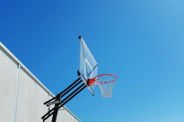 美しい澄んだ空の下でのバスケットボールのフープのローアングルショット