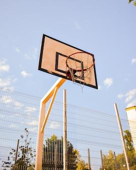 Снимок баскетбольного кольца с цепной сеткой под низким углом на фоне голубого облачного неба
