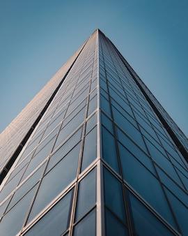 青空の下に窓がある美しくモダンな高層ビルのローアングル ショット