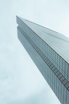 青い空と美しいガラスの近代的な高層ビルのローアングルショット