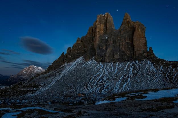 어두운 하늘 아래 눈으로 덮여 아름다운 바위 절벽의 낮은 각도 샷