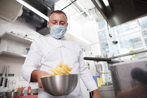 Низкий угол обзора: повар в медицинской маске готовит картофель фри в ресторане