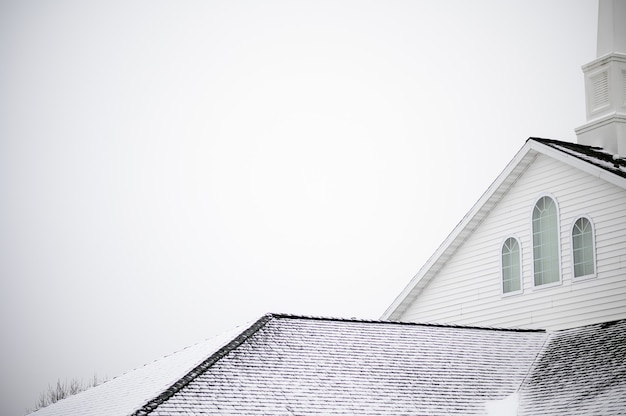 밝은 하늘 아래 스테이플이있는 교회의 낮은 각도 샷