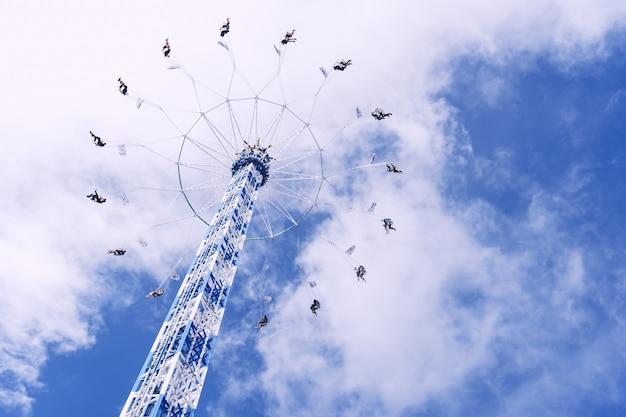 Снимок круговой карусели, вращающейся под небом, полным облаков, под низким углом