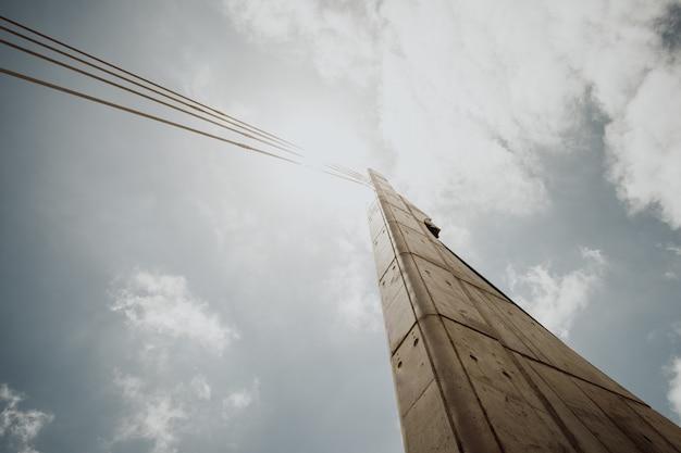 明るい曇り空を背景にしたケーブル付きコンクリート柱のローアングルショット