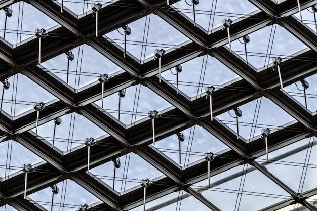 Снимок стеклянного потолка здания с интересными узорами под низким углом