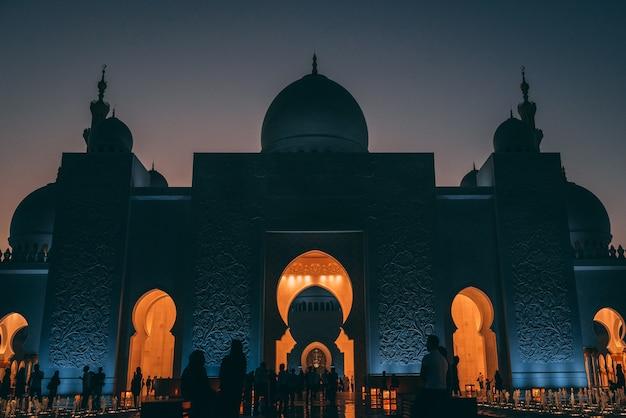 Снимок большой мечети в абу-даби с горящими огнями внутри здания под низким углом