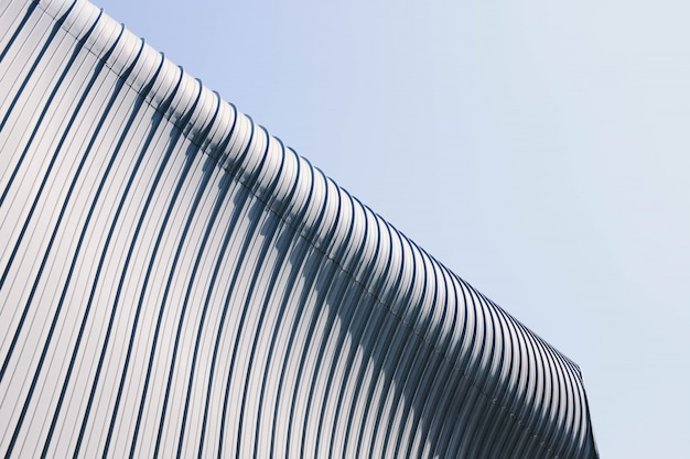 푸른 하늘 아래 재미있는 텍스처와 회색과 흰색 건물 지붕의 낮은 각도 샷