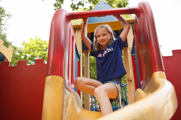 夏に公園で遊び場の滑り台を楽しんでいる幸せな子供のローアングルショット