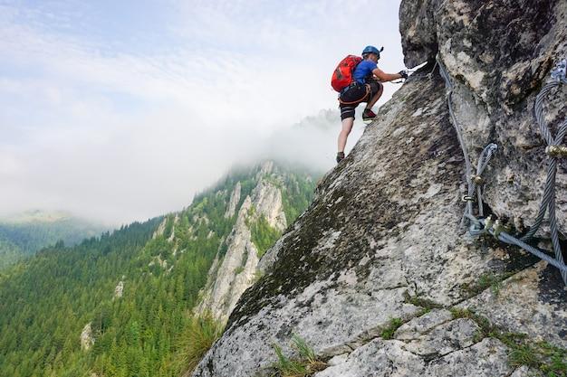 Снимок под низким углом альпиниста-мужчины, поднимающегося на скалу