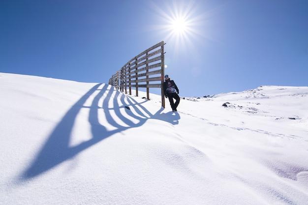 햇빛 아래 눈 덮인 산봉우리에 서있는 남성의 낮은 각도 샷