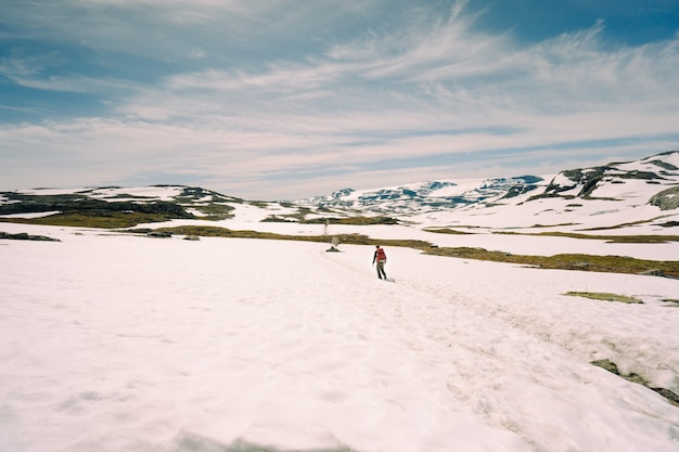 눈 덮인 언덕을 걷는 남자의 낮은 각도 샷