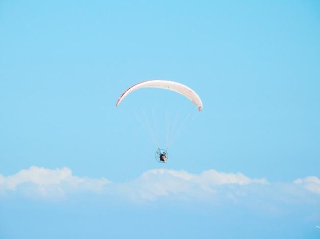 美しい曇り空の下をパラシュートで下る人のローアングルショット