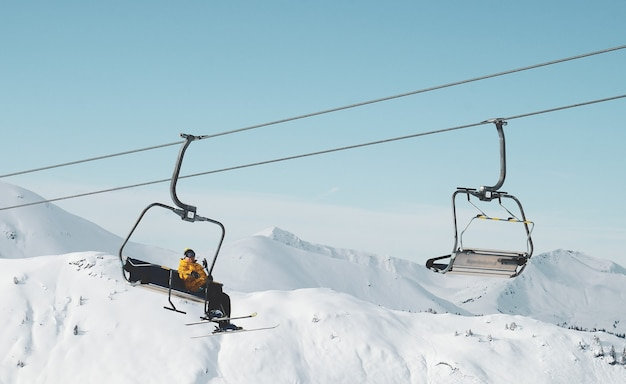 눈 덮인 산에서 케이블카에 앉아있는 사람의 낮은 각도 샷