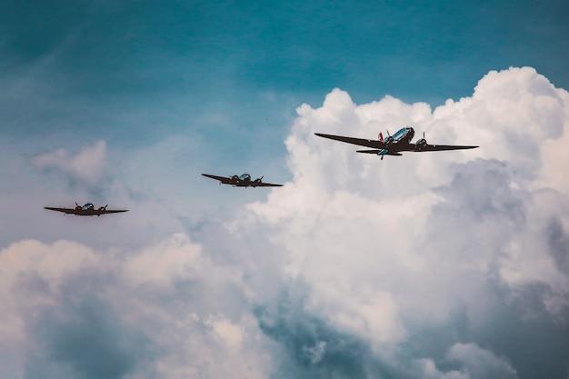 Низкий угол выстрела ряда самолетов, готовящих авиашоу под захватывающим облачным небом