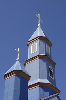 파란색과 맑은 하늘 아래 작은 파란색 교회의 낮은 각도 샷