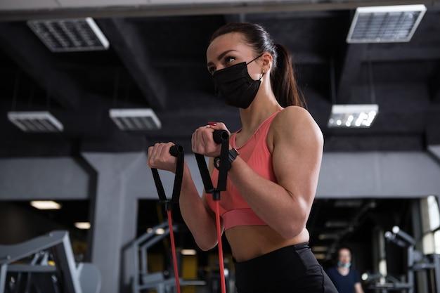 체육관에서 의료 얼굴 마스크를 쓰고 저항 밴드 팔뚝 곱슬을하고 운동가의 낮은 각도 샷