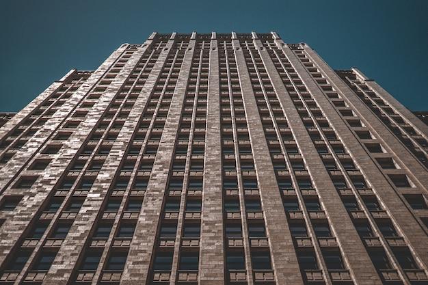 어두운 파란색 배경으로 고층 빌딩의 낮은 각도 샷