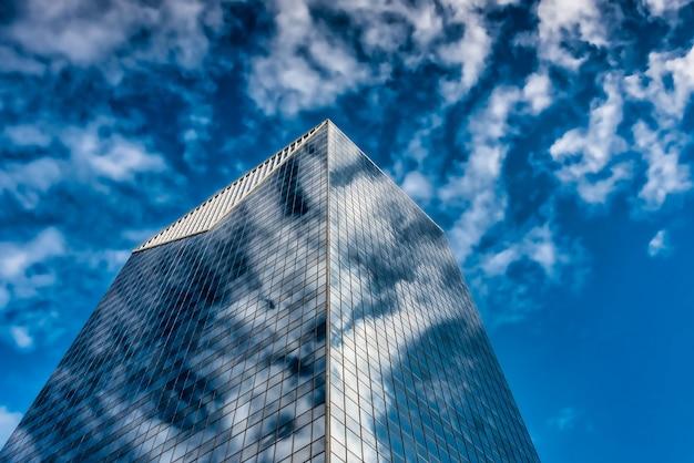 푸른 흐린 하늘 아래 고층 유리 건물의 낮은 각도 샷