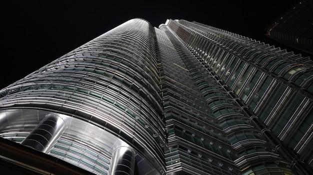 밤에 키가 큰 금속 및 유리 건물의 낮은 각도 샷