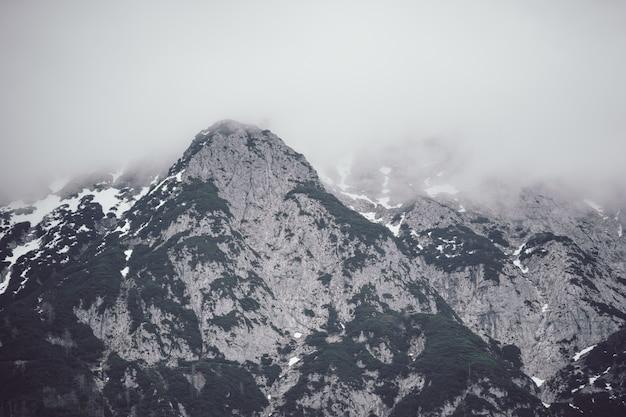 Низкий угол обзора высокой скалистой горы, покрытой густым туманом