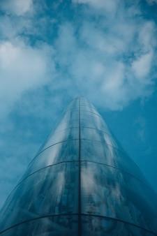 オスロノルウェーの曇りの青い空を反映したタワーのローアングルショット