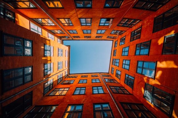 空に触れるユニークな高層オレンジ色の建物のローアングルショット
