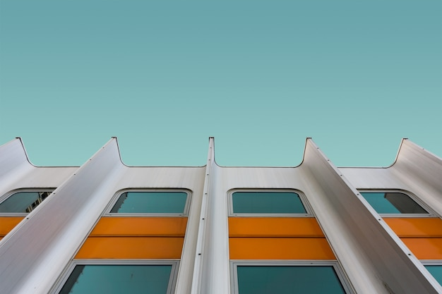 青空の下で白と黄色のモダンな建物のローアングルショット